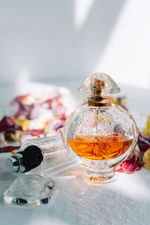 Perfume bottles with fresh water drops on white background with dried colorful flowers petals.