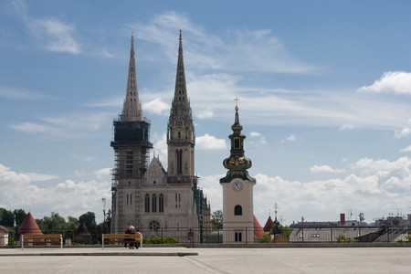 restauration: Grandmother is teaching her gradson about the history of Zagreb. In front them there is a cathedral and old church tower in Zagreb.