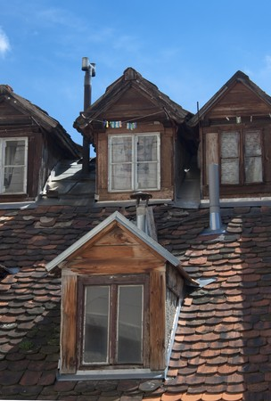 Four really old dormers under a blue sky. photo
