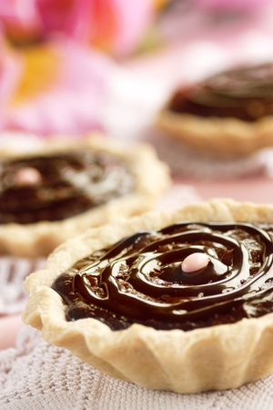 Delicious chocolate tarts with chocolate frosting and pink background. photo
