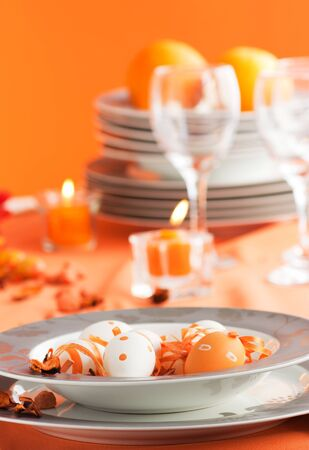 Easter table setting in orange tones with candles and flower. photo