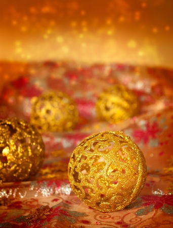 Golden Christmas ornaments on glitter tablecloth. photo