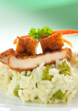 Chicken fried with eggs and bread crumbles and served with peas risotto photo