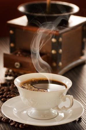 Kopp kaffe framför vintage kaffekvarn.