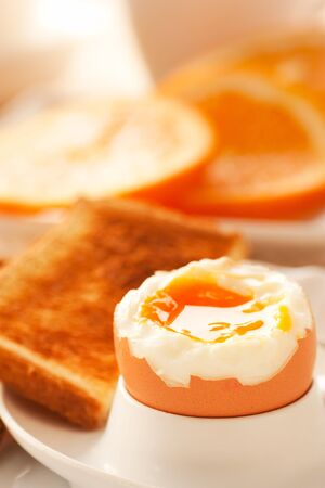 eggcup: Soft boiled egg with toasted bread and slices of oranges in the back. Shallow depth of filed. Stock Photo