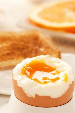 Soft boiled egg with toasted bread and slices of oranges in the back. Shallow depth of filed. photo