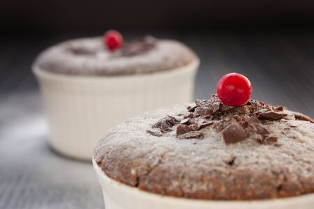 Chocolate souffle with chocolate chips and red currant photo