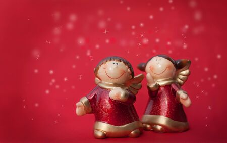 Two Christmas angels figurines on the red background photo