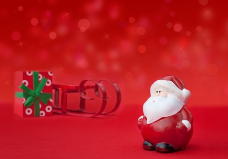 Santa Claus with sledge and present and defocused lights. photo