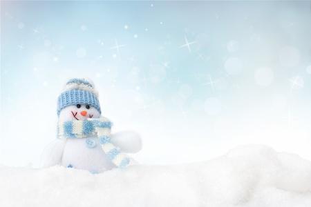 snow scene: Snowman toy on the bokeh winter background