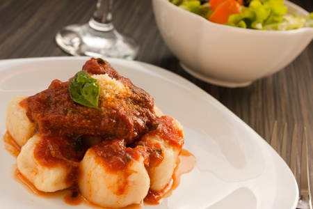 Beef with sauce, gnocchi and salad.