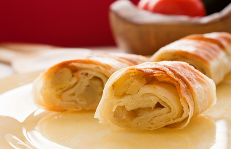 turkish bread: Potato filo pastry with vegetables and cutlery in the back.