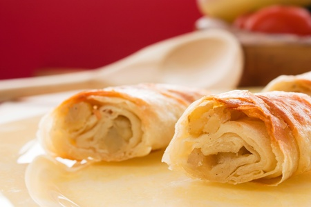 filo: Potato filo pastry with vegetables and cutlery in the back.