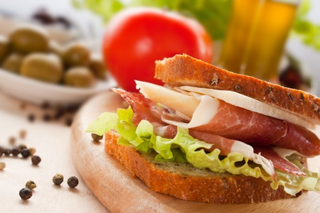Prosciutto and cheese sandwich with olives and lettuce. photo