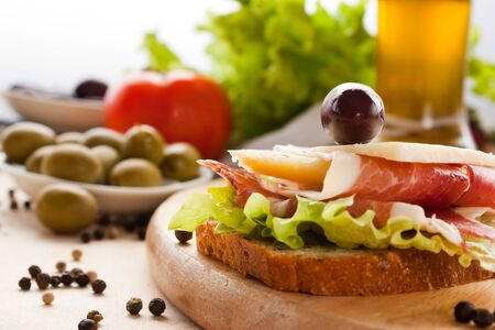 Prosciutto and cheese sandwich with olives and lettuce.Focus is on the cheese. Shallow depth of field. photo