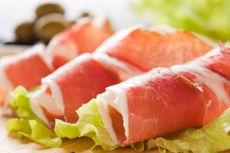 salami sausage: Slices of prosciutto rolled up and arranged on a lettuce leaf. Shallow depth of field.