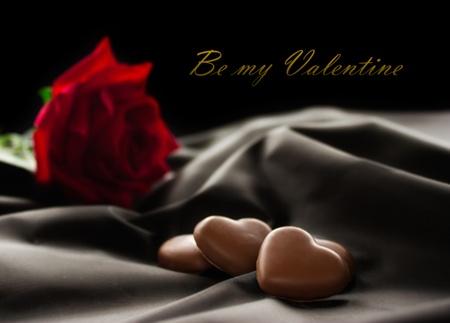 Choklad hjärtan på tyg med röd ros. Tillgängligt utrymme för din text. Stockfoto