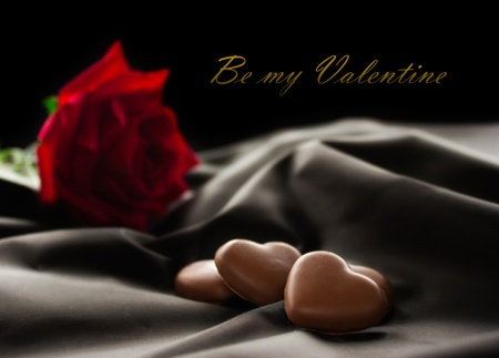 raso: Cuori di cioccolato su tessuto con rosa rossa. Spazio disponibile per il testo.