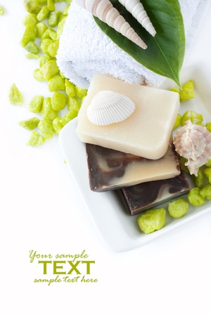 Spa setting with natural soaps, shampoo, towel and shells