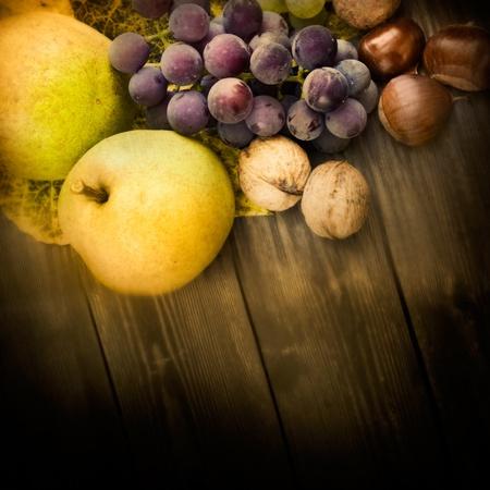 Fondo de naturaleza de fruta de otoño y hermosa luz del sol en la espalda. Uvas, castaña, hoja de vid, nueces, membrillo y manzanas. Foto de archivo - 10682495