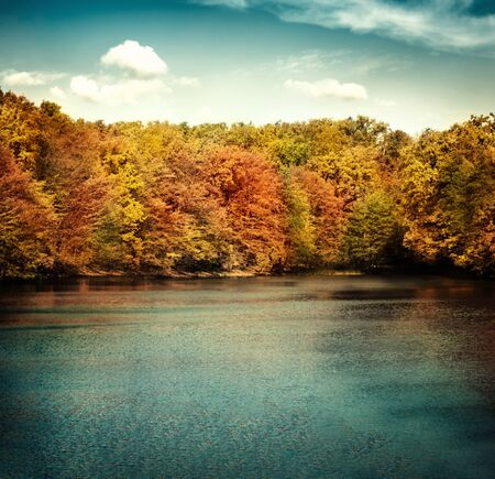 Nature landscape with beautiful lake in autumn with colorful trees and blue sky with cloudscape in the background. Stock Photo - 10682552