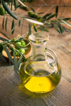 olive leaf: Aceite extra virgen de oliva con aceitunas sanas frescas en el fondo de madera r�stica