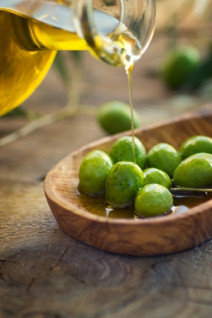 健康的なオリーブ オイルと素朴な木製の背景に新鮮なオリーブ