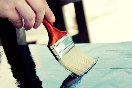 Carpenter is painting wooden furniture for protection photo