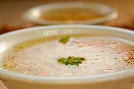 chunky: Clear vegetable soup close up. Shallow depth of field. Stock Photo