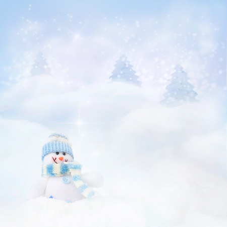 Christmas blue background. Snowman toy on the bokeh winter background in the snow and magical forest with Christmas shiny trees. photo
