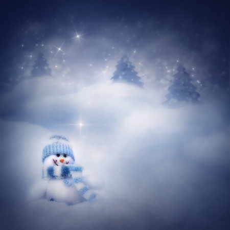 Christmas blue background. Snowman toy on the bokeh winter background in the snow and magical forest with Christmas shiny trees.