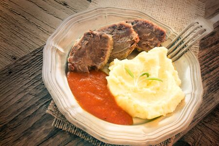 Healthy eating. Boiled beef with mashed potates and tomato sauce in rustic wooden setting photo