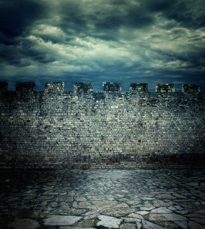 Old rough brick wall background texture. Ancient medieval wall and tiled floor with dramatic cloudscape photo