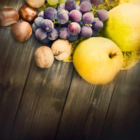 membrillo: Fondo de naturaleza de fruta de oto�o y hermosa luz del sol en la espalda. Uvas, casta�a, hoja de vid, nueces, membrillo y manzanas.