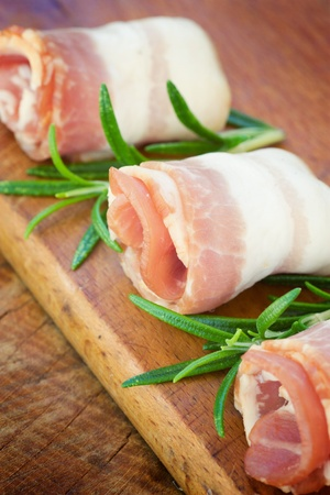 bacon fat: Slices of rolled bacon with rosemary Stock Photo