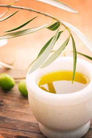 Extra virgin healthy Olive oil with fresh olives on rustic wooden background photo