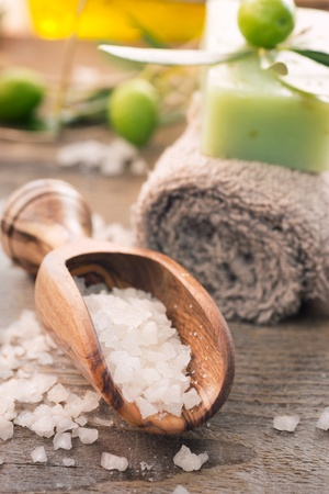Natural spa setting with olive  and olive oil products: bath salt, natural soap and olive oil.