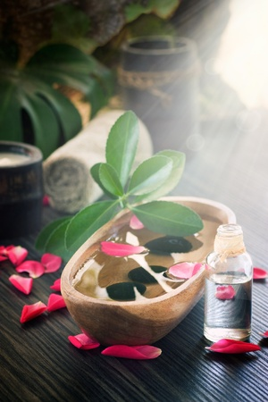 Natural spa setting with rose water and towel. photo