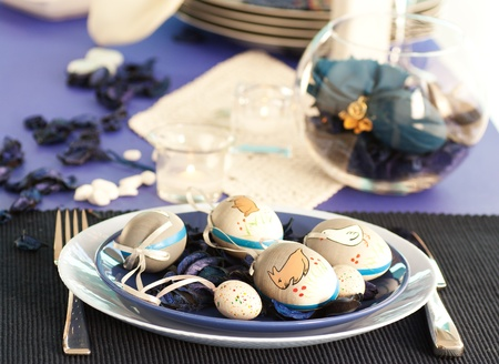 Easter table setting in blue and white tones with candles and flower. photo