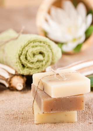 Spa setting with natural soaps and lotus flower. Focus is on the bow. photo