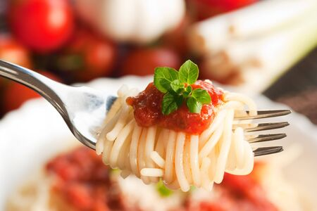 Spaghetti with tomato sauce and ingredients. Cherry tomatoes, onions, garlic and oregano. photo
