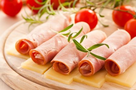 Slices of ham and cheese with rosemary photo