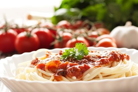 Spaghetti with tomato sauce and ingredients. Cherry tomatoes, onions, garlic and parsley. photo