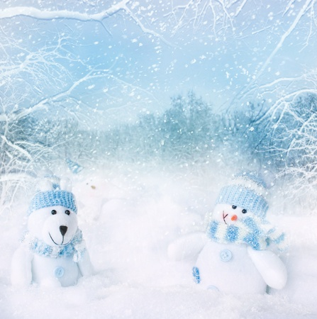 Christmas blue background. Snowman and polar bear toy on the bokeh winter background in the snow
