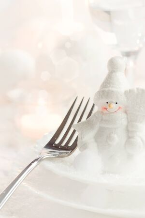 Christmas table setting. Fork and knife in elegant holiday setting with snow and white ornaments photo