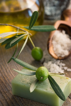 Natural spa setting with olive  and olive oil products: bath salt, natural soap and olive oil. photo