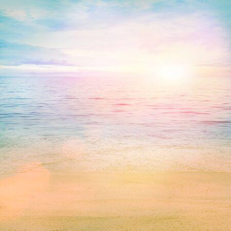 El verano o la primavera de fondo abstracto. Arena dorada con el océano azul y con nubes y puesta de sol en la espalda.