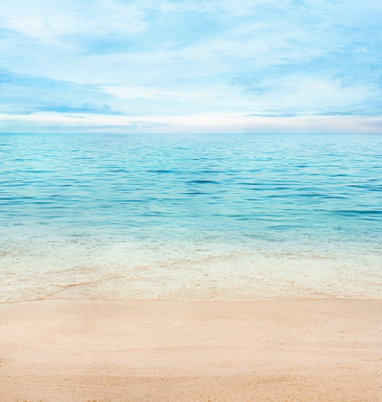sunrise beach: Summer or spring abstract background. Golden sand with blue ocean and cloudscape and sunset in the back.