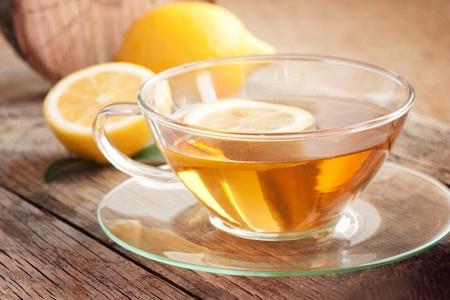 Cup of organic  lemon fruit tea on nature wooden background photo