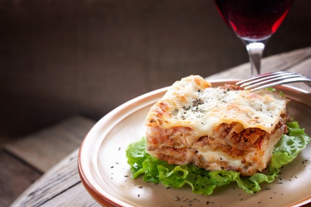 lasagna: Italian cuisine  Freshly baked homemade lasagna with minced meat and cheese served on a piece of lettuce and red wine